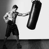 pic of boxing day  - Full length of a shirtless muscular boxer with punching bag in gym - JPG