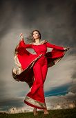 stock photo of cloudy  - Fashionable beautiful young woman in red long dress posing outdoor with cloudy dramatic sky in background - JPG