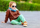 stock photo of bomber jacket  - stylish boy in leather jacket posing on the ground - JPG