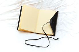 foto of leather-bound  - An old fashioned leather bound blank journal open to show blank pages shot over white fabric - JPG
