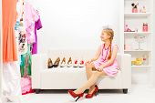 stock photo of braids  - Beautiful small girl with braids sitting on sofa choosing high heels shoes in row in the shop - JPG
