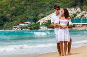 foto of girl walking away  - Lovely happy couple wearing sunglasses walking on a tropical beach - JPG