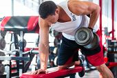 stock photo of lifting weight  - Bodybuilding man exercising lifting dumbbells in fitness club or gym - JPG