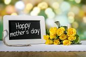 pic of slating  - Image of a slate blackboard with message Happy mothers day on a wooden table with yellow roses - JPG