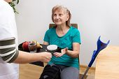 foto of handicap  - A nurse brings a tray with fruit and medicines to a handicaped patient - JPG