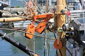 stock photo of pulley  - Orange painted pulleys holding the rigging for pulling in