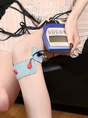 stock photo of stimulation  - Woman using electro stimulation therapy on her knee - JPG