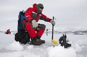 stock photo of auger  - Ice fishermen fishing on a cold overcast day - JPG