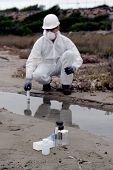 picture of smog  - Worker in a protective suit examining pollution in the water at the industry.
