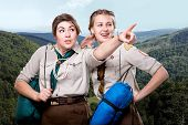stock photo of sleeping bag  - Two young scout girls with sleeping bags traveling in the mountains - JPG