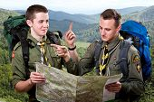 stock photo of boy scout  - Two young scout boys with backpacks holding the map and showing the right way traveling in the mountains - JPG