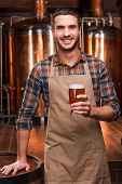 stock photo of apron  - Happy young male brewer in apron holding glass with beer and smiling while standing in front of metal containers - JPG