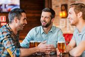 stock photo of excite  - Three happy young men in casual wear talking and drinking beer while sitting in bar together - JPG
