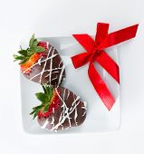 stock photo of dipping  - hand dipped and decorated chocolate covered strawberries with a red bow on a white plate