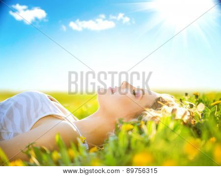 Beautiful Healthy Girl lying on summer field with flowers. Outdoors. Enjoy Nature. Healthy Smiling G