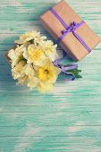 picture of gift wrapped  - Bunch of fresh spring yellow daffodils flowers amd wrapped gift box on turquoise painted wooden planks - JPG