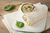 stock photo of sandwich wrap  - sandwich wrap or tortilla with leftover meat cheese and lettuce on wooden background - JPG