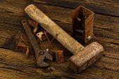pic of braces  - corner braces screws screwdriver sledge hammer and adjustable wrench on wooden background - JPG