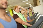 stock photo of fat woman  - Exhausted fat woman training on running machine in gym - JPG