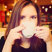 stock photo of sweetie  - young woman is drinking in modern cafe - JPG