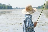 picture of chums  - Angler boy is chumming handmade fishing rod back view shot - JPG