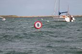 stock photo of restriction  - A Boat Speed Restriction Sign in a Coastal Harbour - JPG