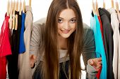 pic of clothes hanger  - Happy teen woman between clothes on hanger - JPG