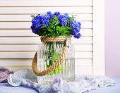 image of blue-bell  - Blue bell flowers in glass vase on wooden background - JPG