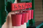 stock photo of fire-station  - A row of red fire buckets hanging at Alton Watercress Line Railway Station - JPG