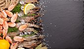 stock photo of tiger prawn  - Fresh prawns with spices on black stone background - JPG