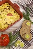 image of leek  - Omelette with tomato and leek baked in red pan and served on white painted wooden table - JPG