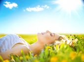 stock photo of happy day  - Beautiful Healthy Girl lying on summer field with flowers - JPG