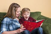 stock photo of singing  - A young child gets ready to read by singing with his mother using a book based on a song - JPG