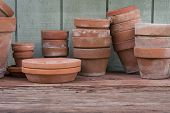 pic of flower pot  - Used terracotta flower pots rest on a gardener - JPG