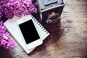 picture of vintage antique book  - Books, notebooks, vintage camera, white smart phone and lilac flowers on an old wooden board background, hipster lifestyle arrangement ** Note: Visible grain at 100%, best at smaller sizes - JPG