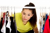 image of clothes hanger  - Young beautiful woman with clothes on hanger - JPG