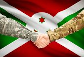stock photo of burundi  - Soldiers shaking hands with flag on background  - JPG