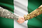 foto of nigeria  - Soldiers shaking hands with flag on background  - JPG
