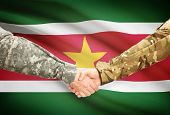picture of suriname  - Soldiers shaking hands with flag on background  - JPG