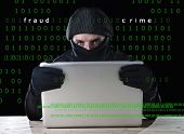 stock photo of computer hacker  - hacker man in black using computer laptop for criminal activity hacking password and private information cracking password too access bank account data in cyber crime concept - JPG