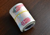stock photo of dirhams  - Hundred dirham notes rolled and tied with rubber band - JPG