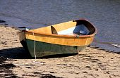 stock photo of dory  - Beautiful wooden dory sitting on the beach at low tide on a sunny summer day - JPG