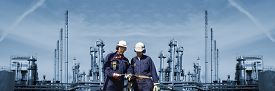 picture of gas-pipes  - oil and gas engineers with large refinery in background - JPG