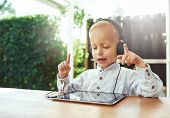 Постер, плакат: Little Boy Immersed In His Music