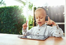 image of conduction  - Little boy immersed in his music gesturing with his hands as he conducts and sings along to the lyric and beat on his headphones as he sits at a table on a patio at home - JPG