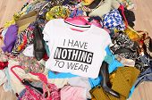 Big Pile Of Clothes Thrown On The Ground With A T-shirt Saying Nothing To Wear. poster