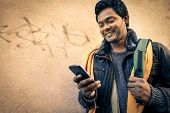 Постер, плакат: Young Indian Man Holding Mobile Phone Cheerful Asian Model Next To Old Urban Wall Soft Vintage F