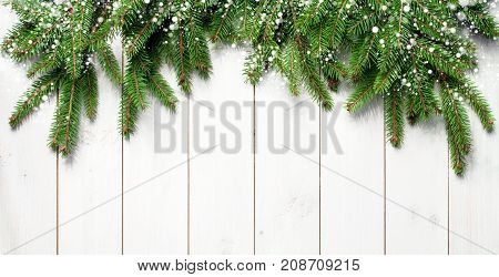 poster of Christmas snow-covered branches on a white wooden background. New Year's background, holiday, christmas, snow, winter, green branches top view with copy space.