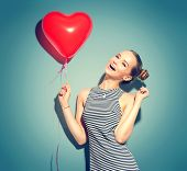 Beauty girl with red heart shaped air balloon laughing over green background. Beautiful Happy woman  poster