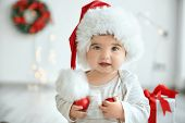 Little baby in Santa hat with Christmas balls on blurred background poster